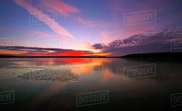 View of the sky and cloud patterns reflected in the frozen surface of a lake.  Royalty-free stock photo