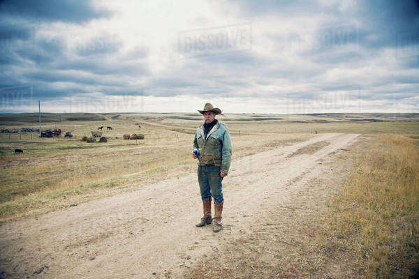 Man wearing cowboy hat and cowboy boots standing on a country lane in the Canadian Prairie. Royalty-free stock photo