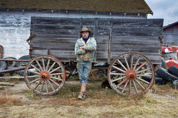 Man in cowboy hat and cowboy boots leaning against a wooden wagon. Royalty-free stock photo