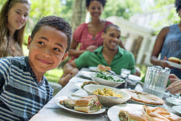 A family gathering, men, women and children around a table in a garden in summer. A boy smiling in the foreground. Royalty-free stock photo