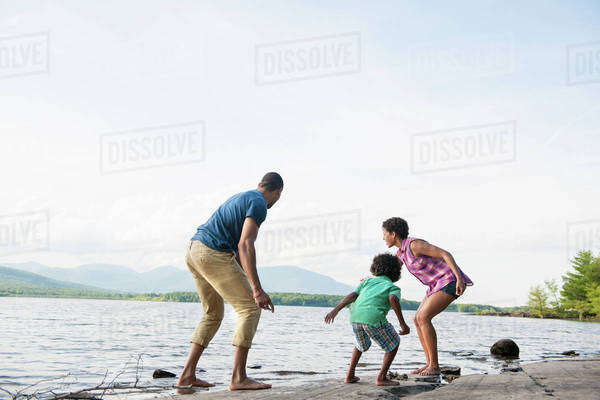 A family, mother, father and son playing on the shores of a lake.  Royalty-free stock photo