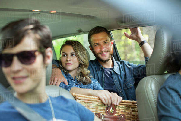 A group of people inside a car, two in the back seat and two in the front.  Royalty-free stock photo