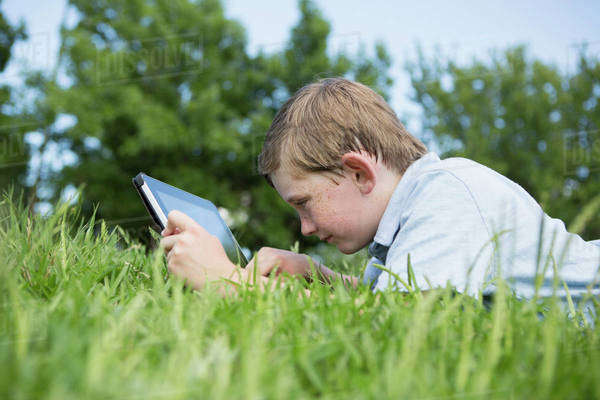 A young boy lying on the grass, using a digital tablet.  Royalty-free stock photo