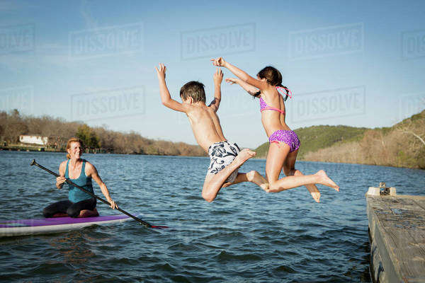 Two children leaping into the water from a jetty. Royalty-free stock photo