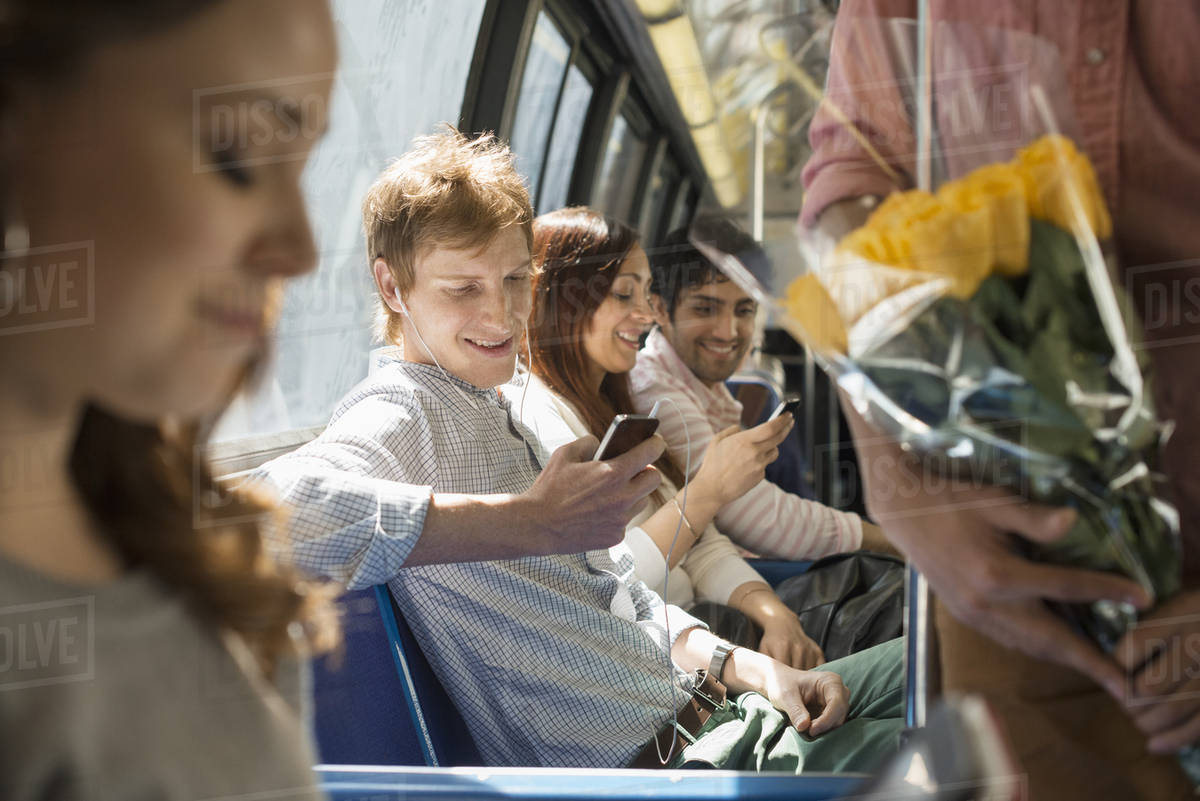 Urban Lifestyle. A group of people, men and women on a city bus, in New York city. Two people checking their smart phones. Royalty-free stock photo