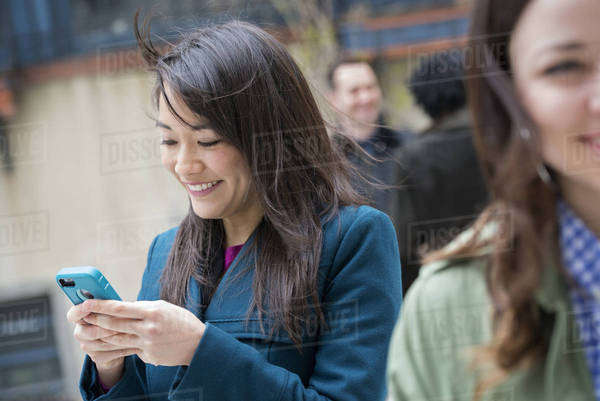 A woman checking her turquoise smart phone, among other people on a city street. Royalty-free stock photo