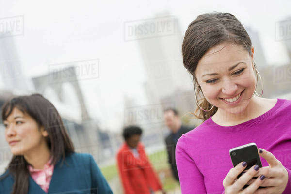 New York city, the Brooklyn Bridge crossing over the East River. Four friends in the park by the river, one woman looking at her phone and smiling.  Royalty-free stock photo