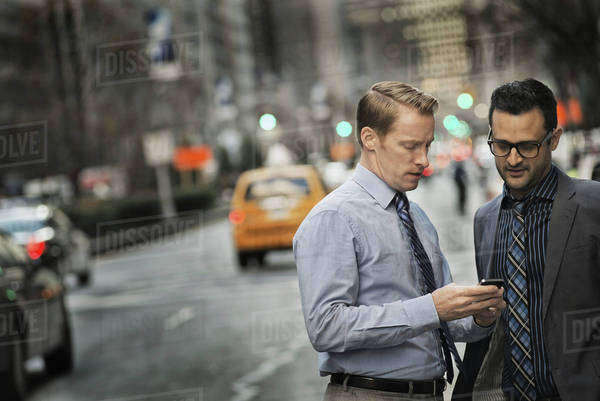 Two men standing together looking at a cell phone display on a busy street at dusk. Royalty-free stock photo