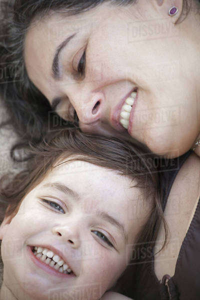 A close up of a mother and daughter lying with their heads together, smiling and laughing. Royalty-free stock photo