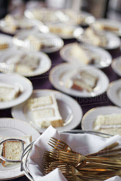 A table laden with plates. White china, and a basket full of dessert forks. A slice of wedding cake.  Royalty-free stock photo