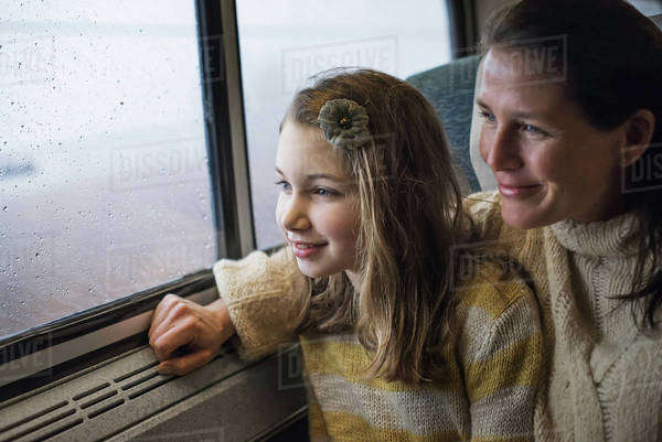 A man and a young girl sitting beside the window in a train carriage looking out at the countryside. Smiling in excitement. Royalty-free stock photo