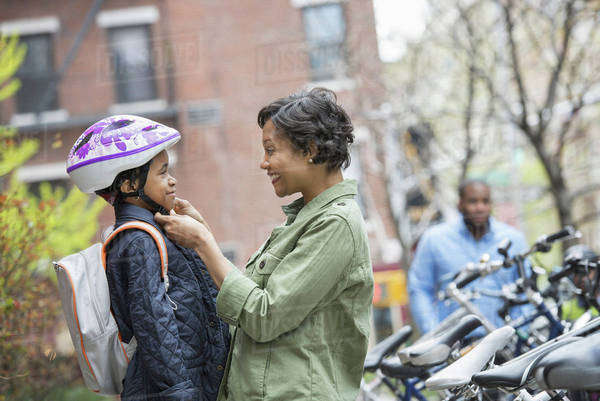 A New York city park in the spring. A boy in a cycle helmet, being fastened by his mother, beside a bicycle rack. Royalty-free stock photo