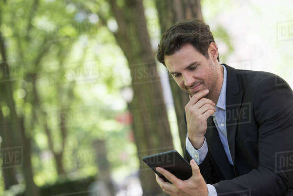 Business people in the city. Keeping in touch on the move. A man sitting in a park using his digital tablet.  Royalty-free stock photo