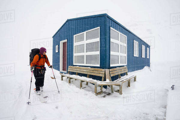 A skier leaving a refuge hut in mist and cloud conditions on the Wapta Traverse, a mountain hut to hut ski tour in Alberta, Canada.   Royalty-free stock photo
