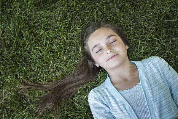 A girl with long hair fanned out, asleep on the grass.  Royalty-free stock photo
