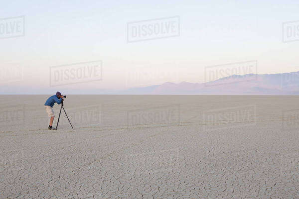 Man with camera and tripod on the flat saltpan or playa of Black Rock desert, Nevada. Royalty-free stock photo