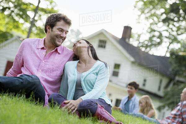 A couple sitting on the grass at a summer party. Royalty-free stock photo