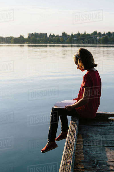 A young girl sitting on a dock, reading a book.  Royalty-free stock photo