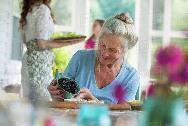 A family party in a farmhouse in the country in New York State. A mature woman holding bowl of fresh blackberries. Royalty-free stock photo