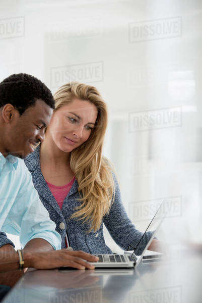 Office Interior. A Couple At A Table Using A Laptop. Royalty-free stock photo