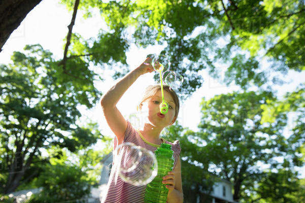 A Young Girl Blowing Bubbles In The Air Under The Branches Of A Large Tree.  Royalty-free stock photo