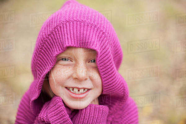 A girl in a magenta hooded sweater, with the hood covering her head, and hands hidden in her cuffs. Keeping warm. Royalty-free stock photo