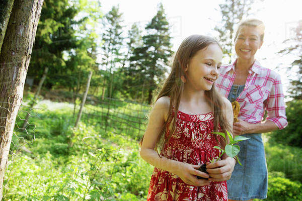 A young girl holding a seedling plant, and walking through the gardens of the farm with an adult woman following. Royalty-free stock photo
