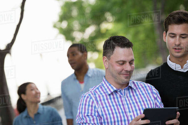 Summer in the city. People outdoors, keeping in touch while on the move. Four people in a group. One using his digital tablet.  Royalty-free stock photo