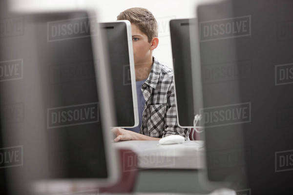 A school room, computer laboratory or lab with rows of computer monitors and seating. A young person seated working at a terminal. Royalty-free stock photo