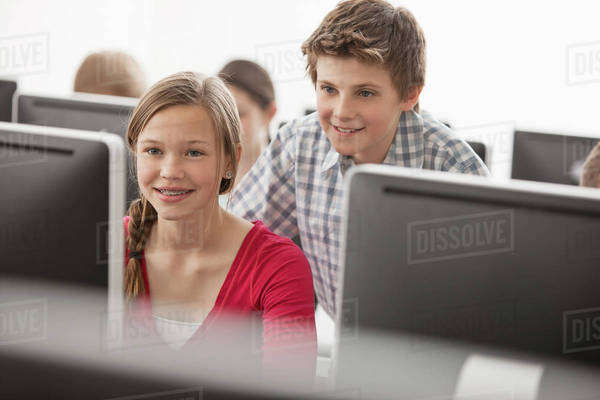 A school computer lab room, with rows of screens. Two young people looking intently at the screen. Royalty-free stock photo