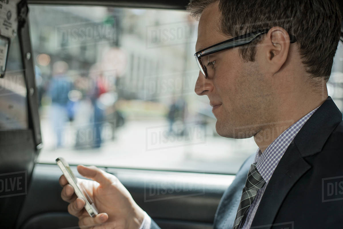 A working day  A man in a yellow cab, using his smart phone  stock photo