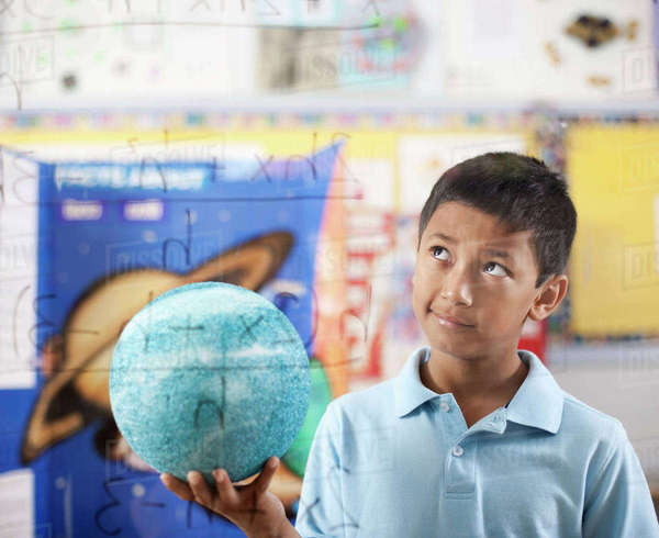 A boy holding a globe, standing by an equation board, looking puzzled and pensive.  Royalty-free stock photo