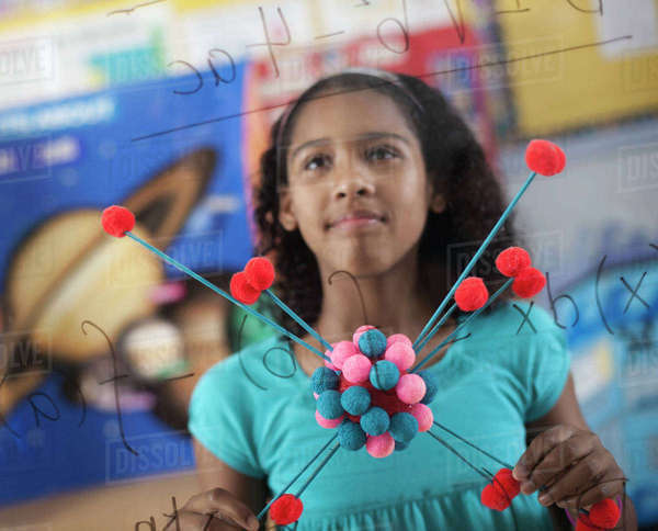 A girl holding a molecular structure and looking at a board of equations and formulae in the classroom. Royalty-free stock photo