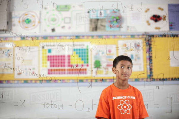 A boy looking at a clear see-through board showing scientific equations and calculations.  Royalty-free stock photo