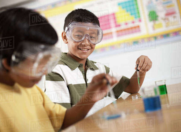 Two young people, boy and girl in a science lesson, wearing eye protectors and working on an experiment.  Royalty-free stock photo