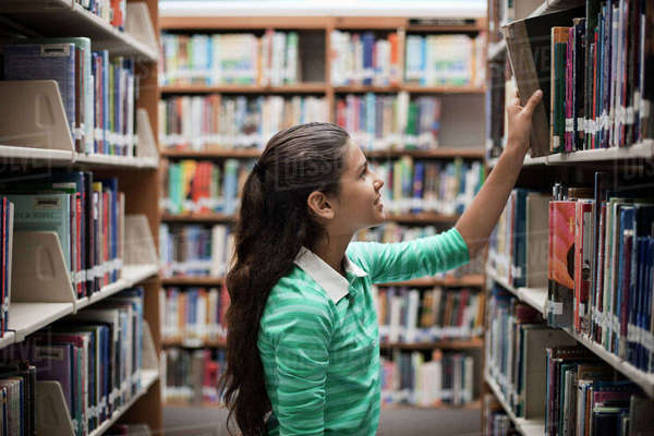 A girl looking at books in a library. Royalty-free stock photo