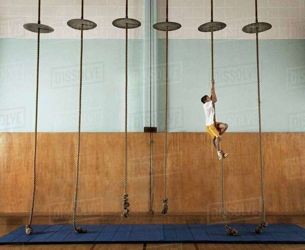 A child climbing up a rope in a school gym.  Royalty-free stock photo