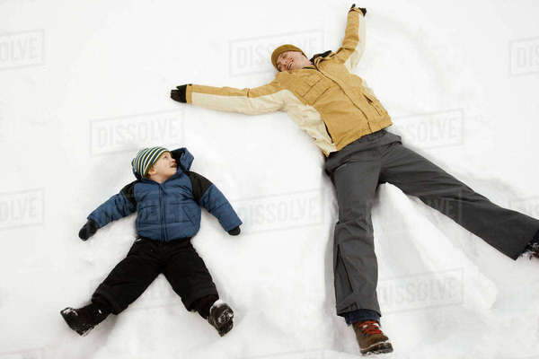 Two people, a man and a child lying in the snow make snow angel shapes.  Royalty-free stock photo