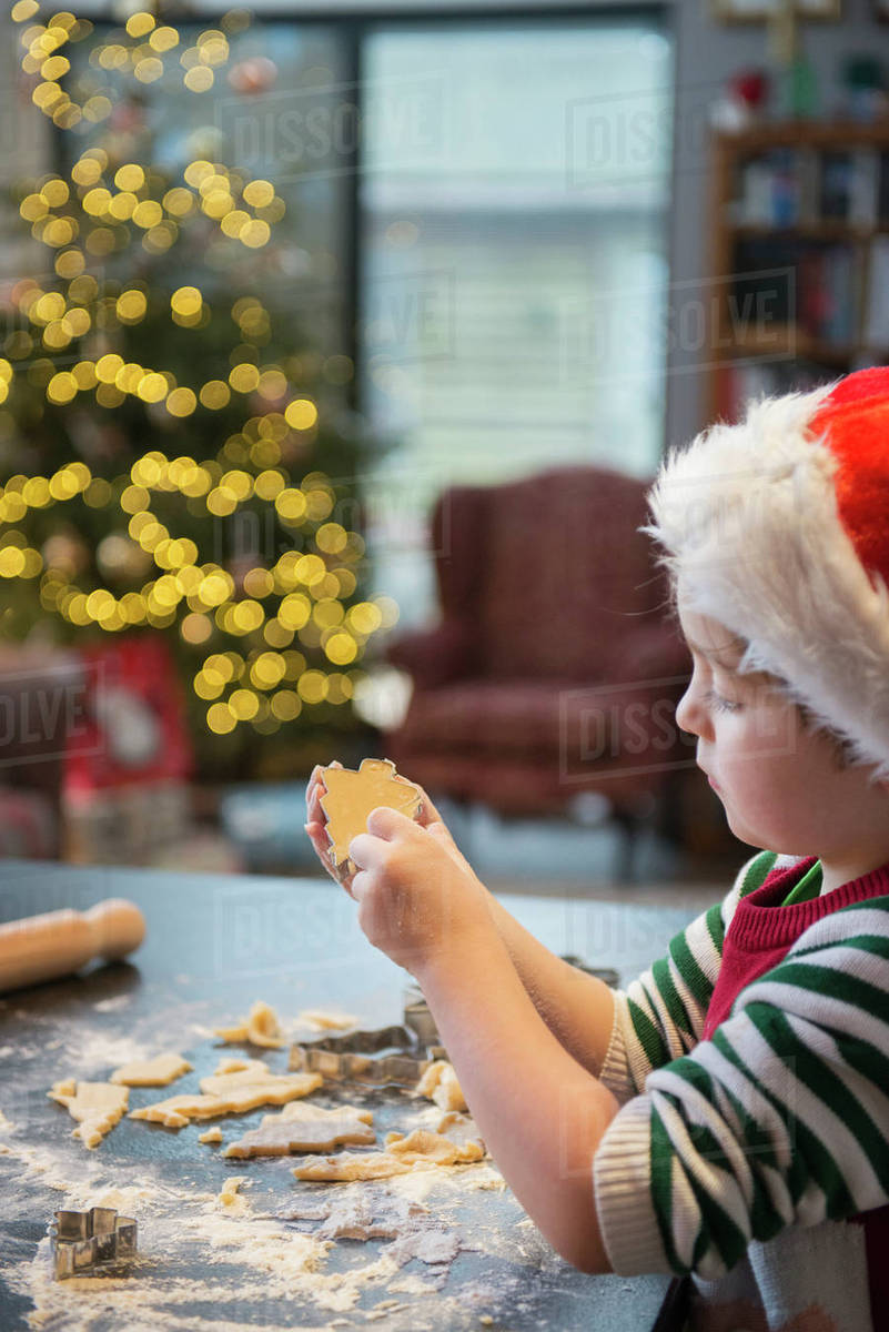 A boy in a Santa hat making Christmas biscuits, cutting out shapes.  Royalty-free stock photo