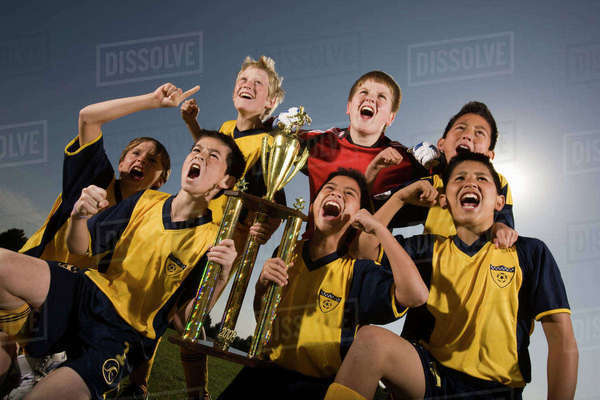 A group of boys in soccer team shirts holding a trophy and celebrating a win.  Royalty-free stock photo