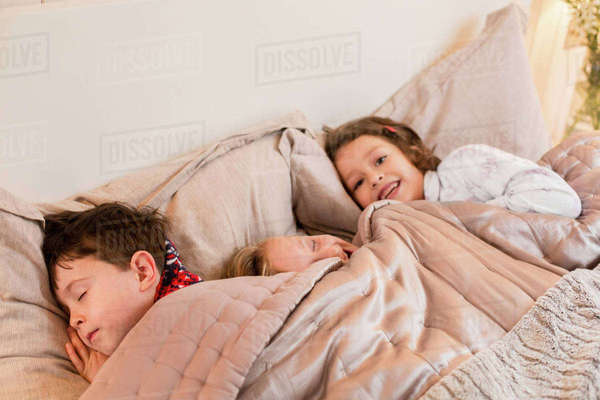 Three children lying in a bed under the covers.  Royalty-free stock photo
