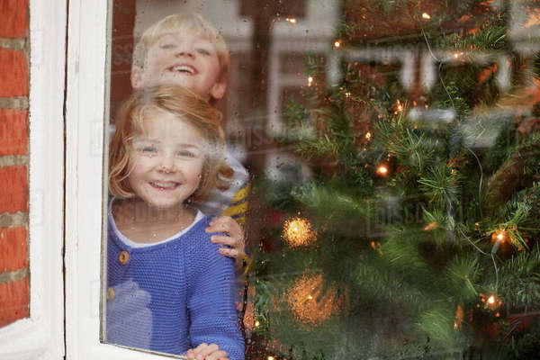 Two children, a boy and girl, looking out of a window at home beside a Christmas tree.  Royalty-free stock photo