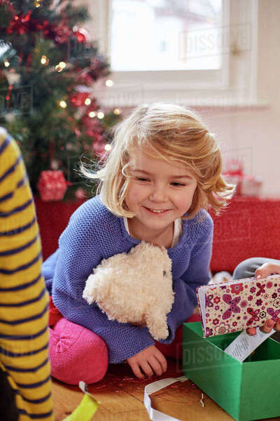 Two children on Christmas Day finding and unwrapping presents at home.  Royalty-free stock photo