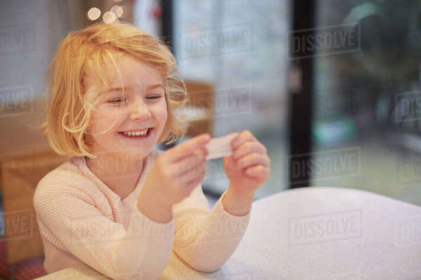 A young girl laughing and looking at a small piece of paper, a joke from a Christmas cracker.   Royalty-free stock photo
