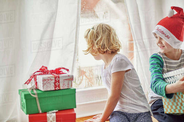 Christmas morning in a family home. A girl on a window seat looking out.  Royalty-free stock photo