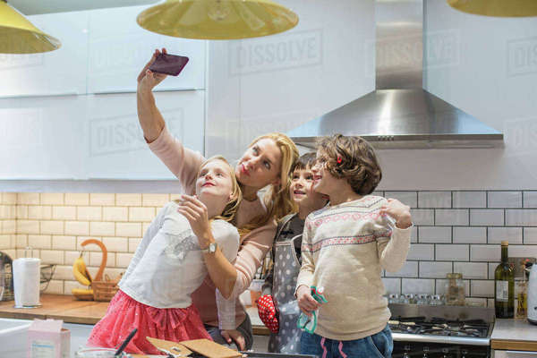 An adult woman and three children taking a selfy photograph in the kitchen. Royalty-free stock photo
