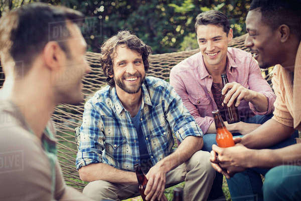 A group of friends lounging in a large hammock in the garden having a beer.  Royalty-free stock photo