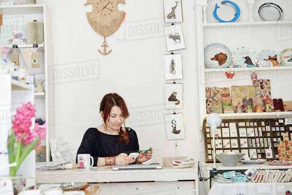 A woman sitting at a desk in a small gift shop, doing the paperwork, managing the business, using a laptop and a smart phone.  Royalty-free stock photo