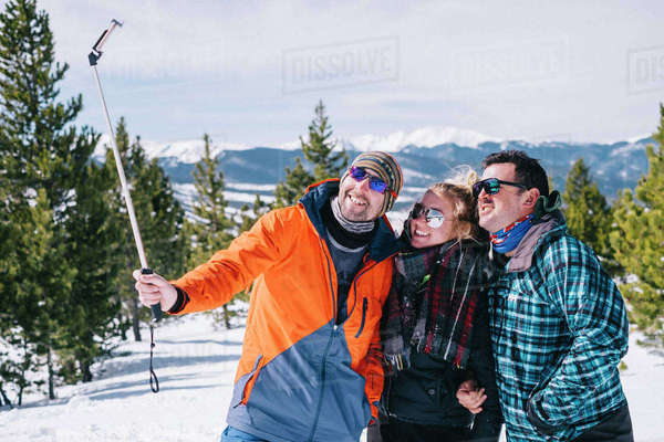 Three people, two men and a young woman in skiing gear posing for a selfie, one holding a selfie stick.  Royalty-free stock photo