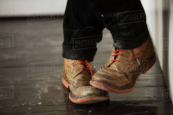 Close up of a man's feet, wearing brown brogues with red shoe laces. Royalty-free stock photo
